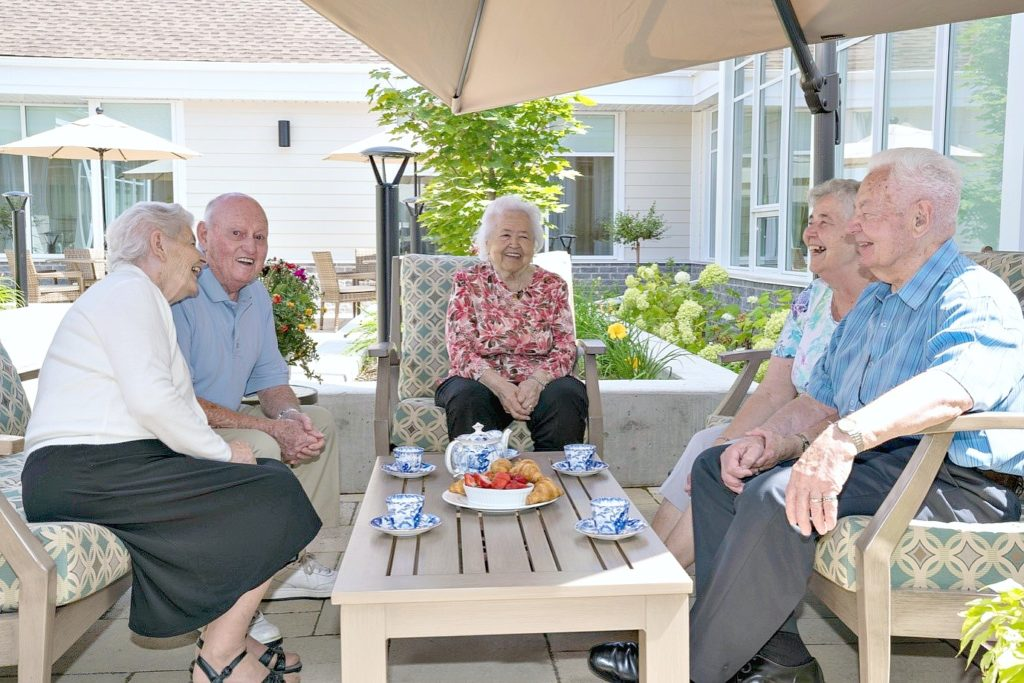 5 elderly people sit and enjoy tea and croissants on a patio.