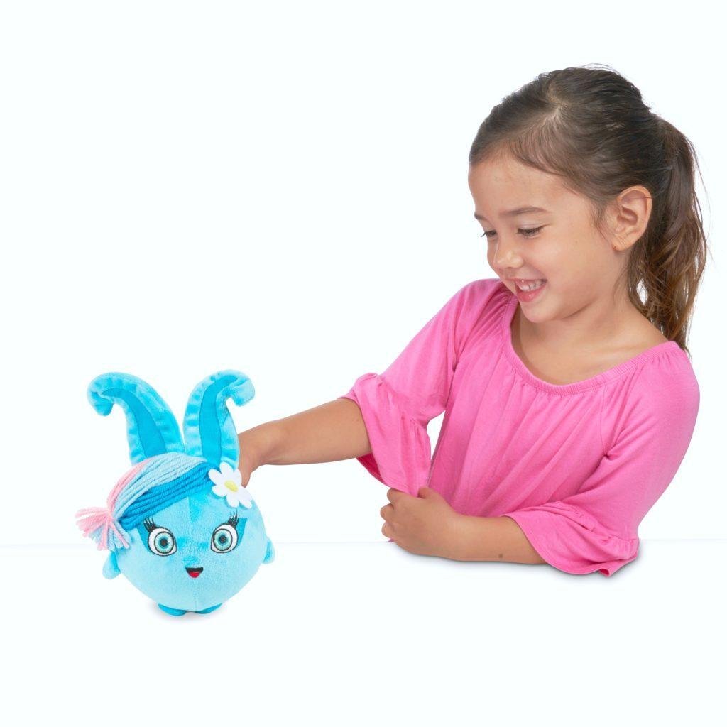 Little girl plays with a blue Sunny Bunny.
