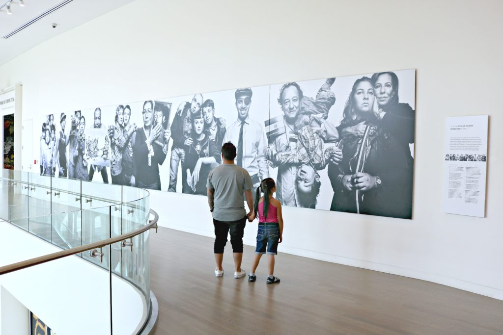 A father and his daughter hold hands while looking at a mural on the wall at the Center for Civil and Human Rights.