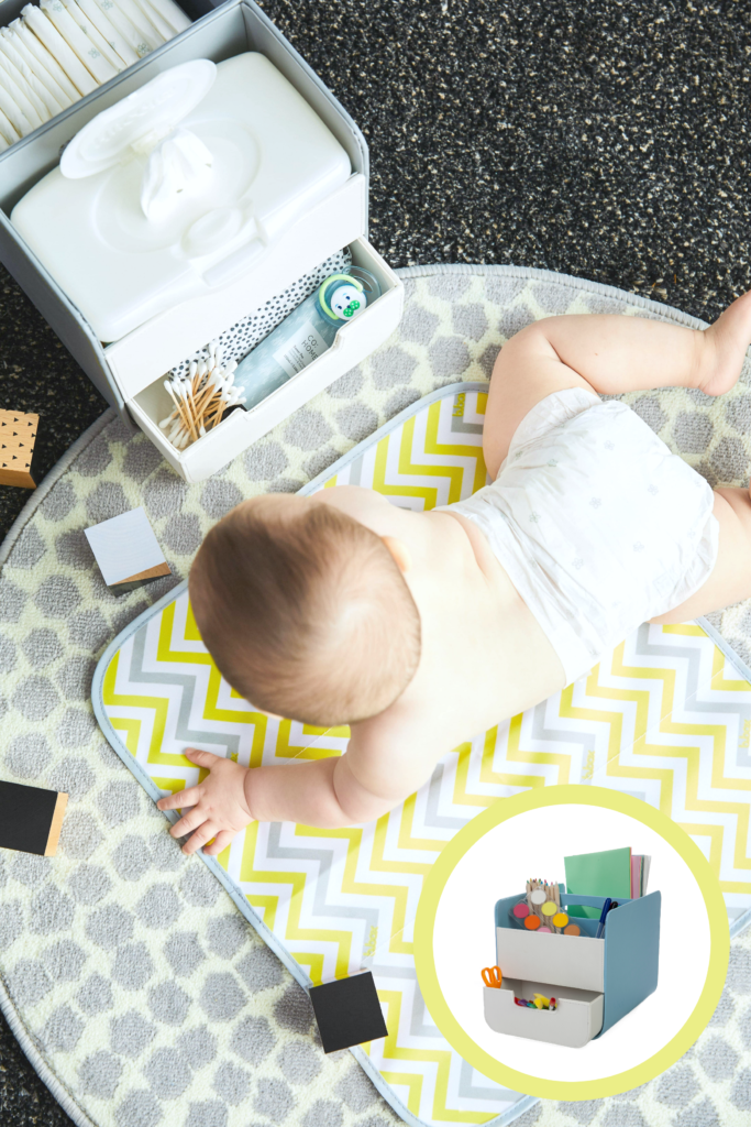 A baby is shown having tummy time on the floor while the bbox Diaper caddy is in picture.