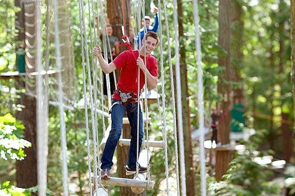 A boy smiles as he goes through a rope course.