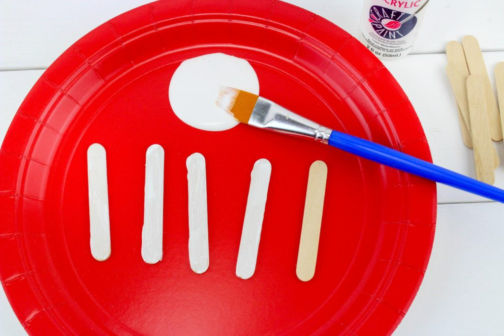 Red plate with white paint and mini popsicle sticks being painted.