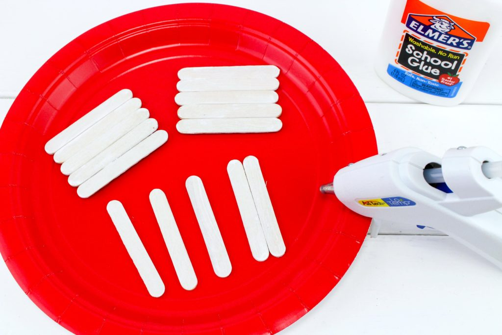 Red plate with mini popsicle sticks being glued together.