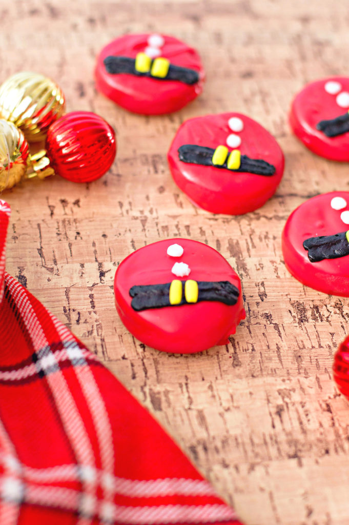 Santa Belt Chocolate Covered Oreos are shown against a cork background with a plaid napkin and mini gold and red ornaments.
