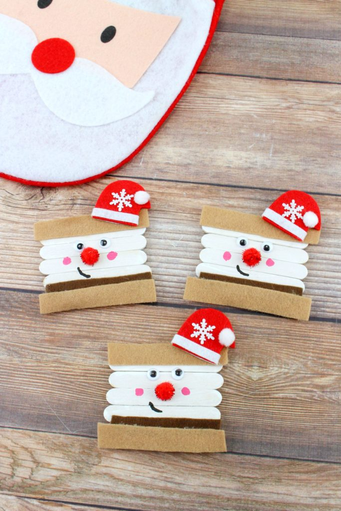 A wood background with a Santa and the Santa S'mores ornament crafts.