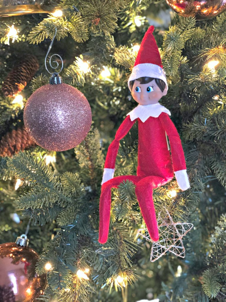 Elf on the Shelf sitting in tree next to ornament.