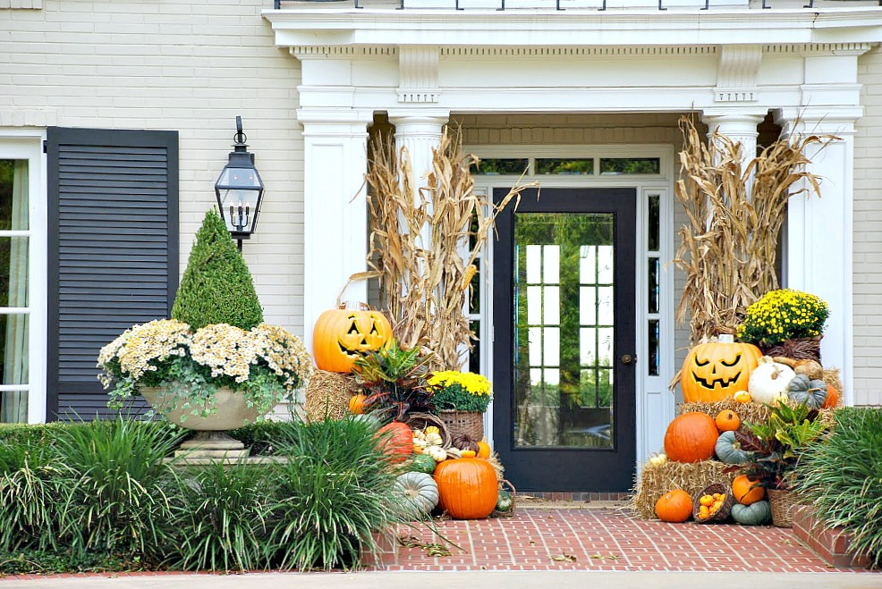 A front porch is decorated with fall decor and pumpkins and squash.