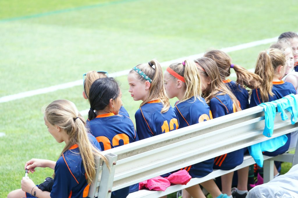 Girls on the bench during soccer game.