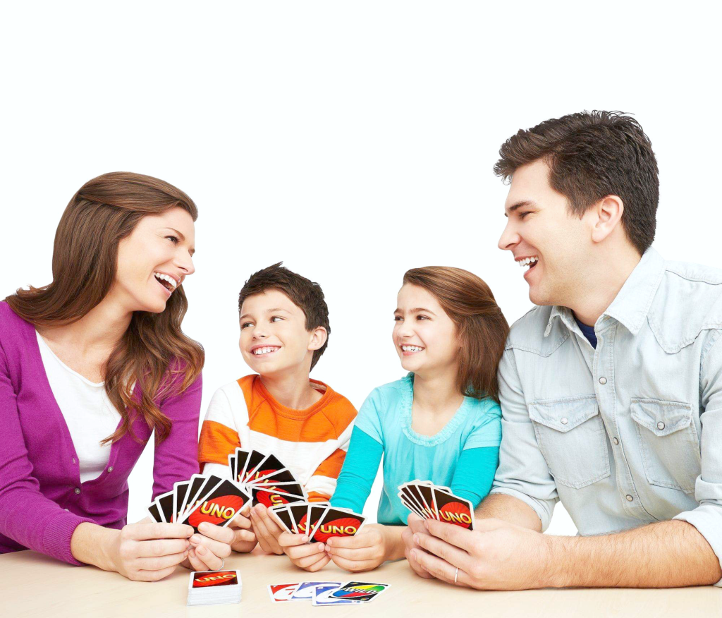 A family plays UNO and are having a blast and laughing.