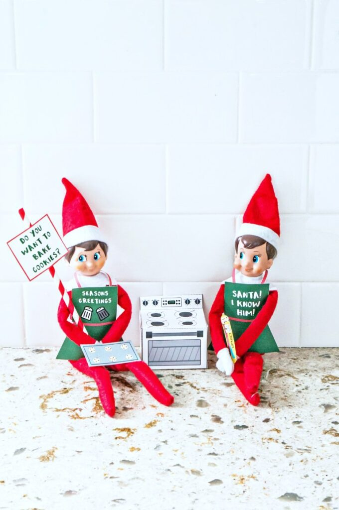 Two elves on the shelf posing with signs and an oven.