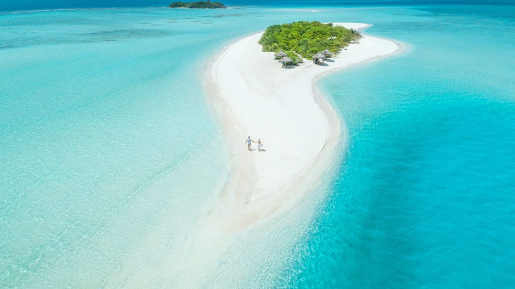 Couple walks on a deserted island in the Maldives.