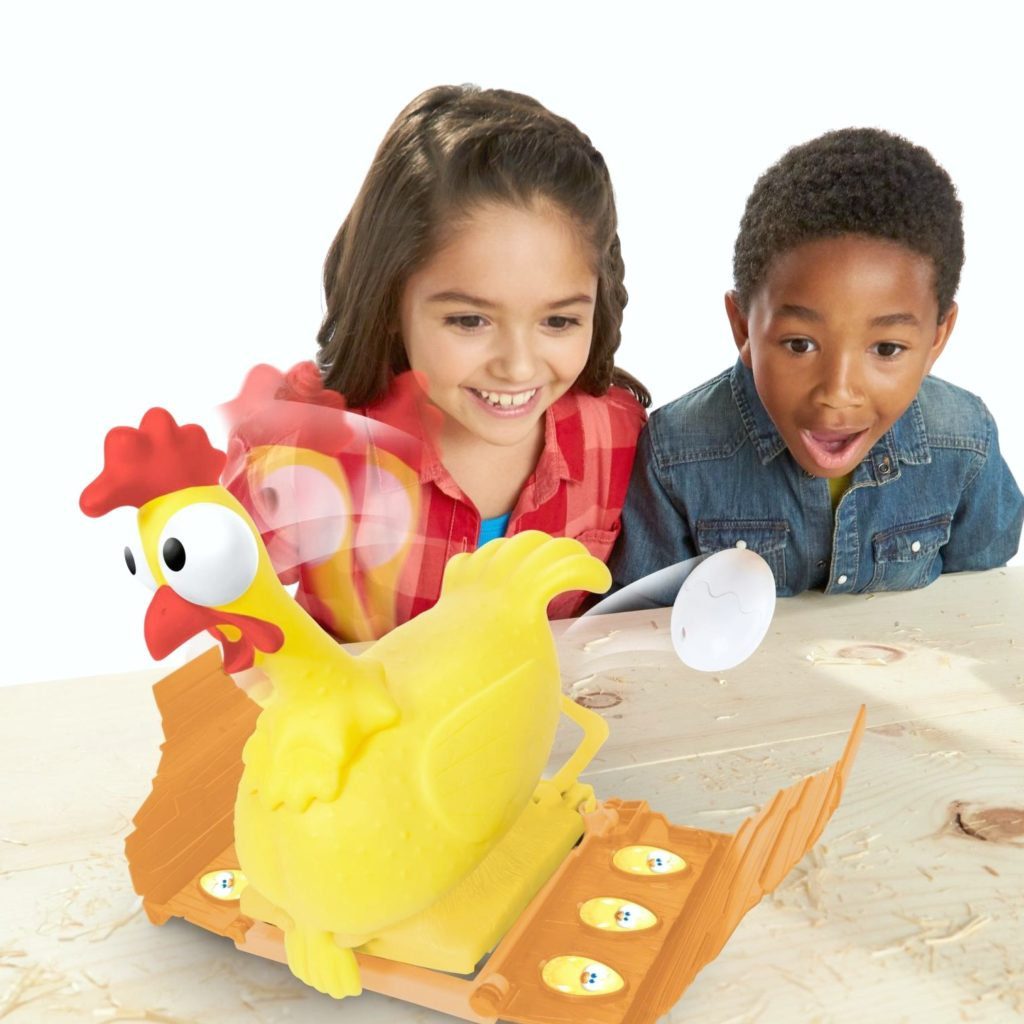 A girl and a boy are at amazed at a flying egg from the Squawk Eggsplosive Chicken Game.