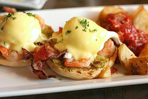 Eggs Benedict on an English muffin with bacon and home fries.