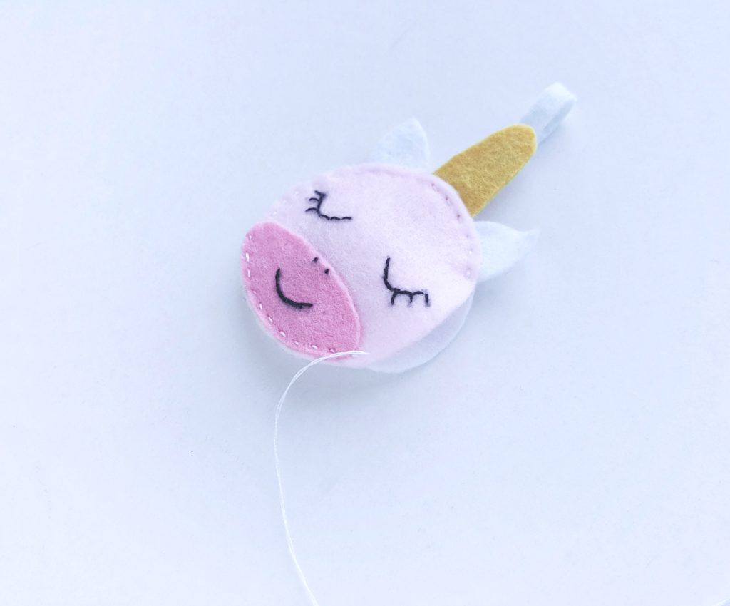 Felt unicorn craft with a hole left on the side to stuff the craft with.