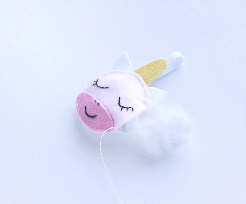 Cotton being stuffed into Felt Unicorn craft ornament.