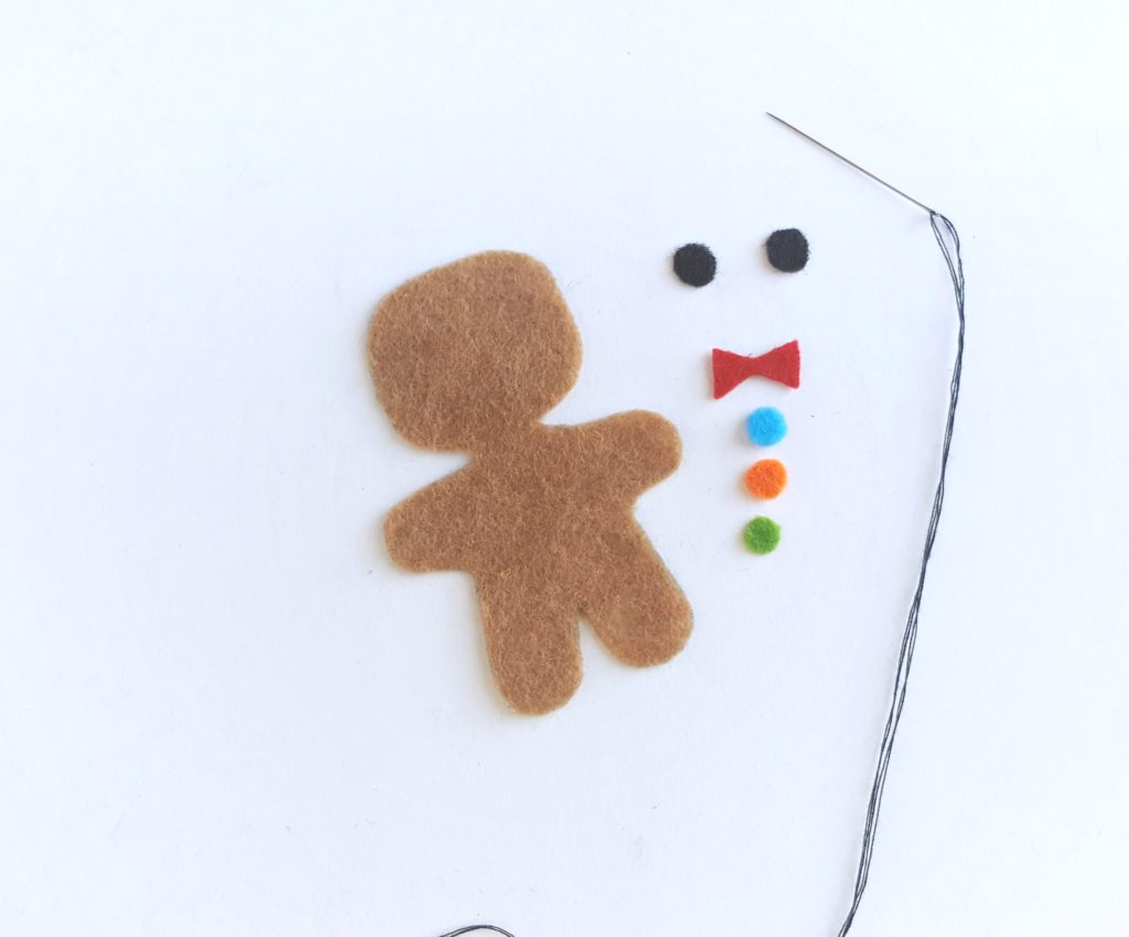 One brown felt cutout of a gingerbread man with eyes, bowtie, and gumdrop buttons.
