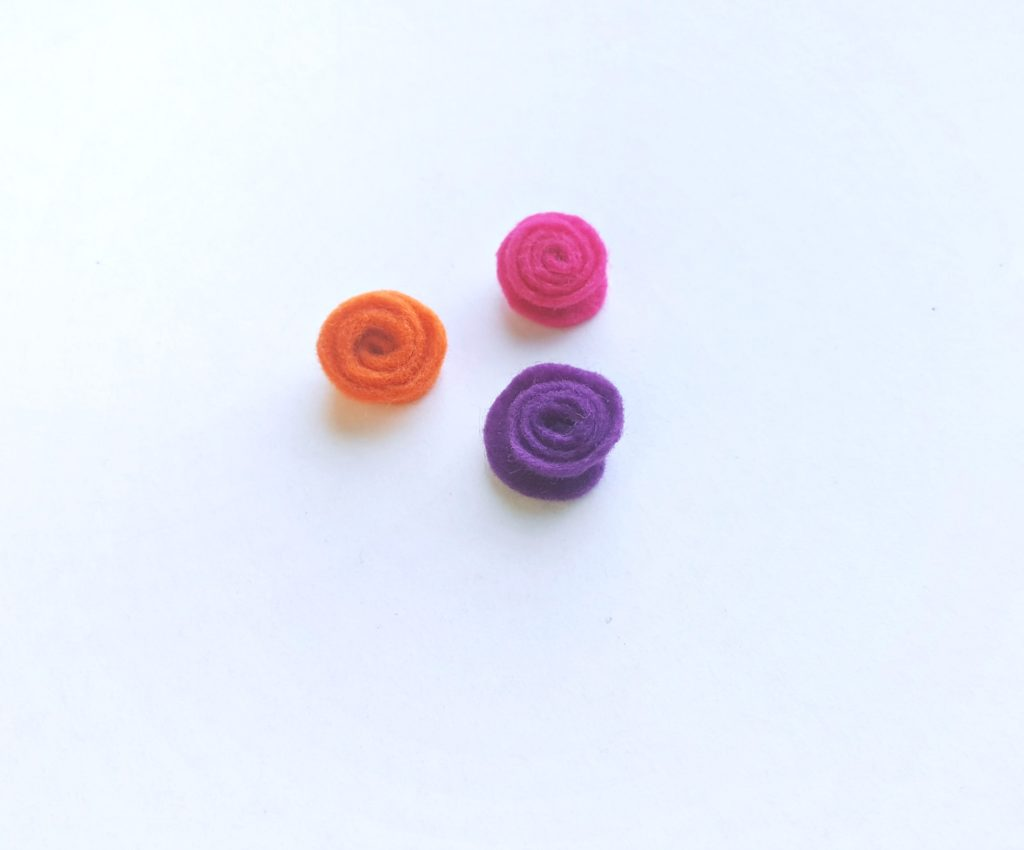 Orange, pink, and purple felt are coiled up into flowers.