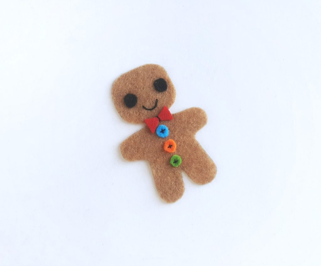 All parts sewn onto brown felt gingerbread man cutout.