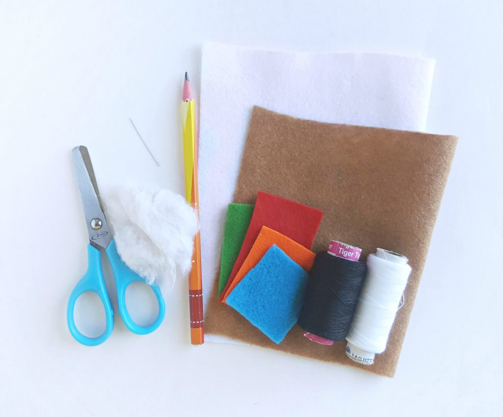 A collection of things needed to make the craft: scissors, cotton, felt, needle and thread, and pencil.