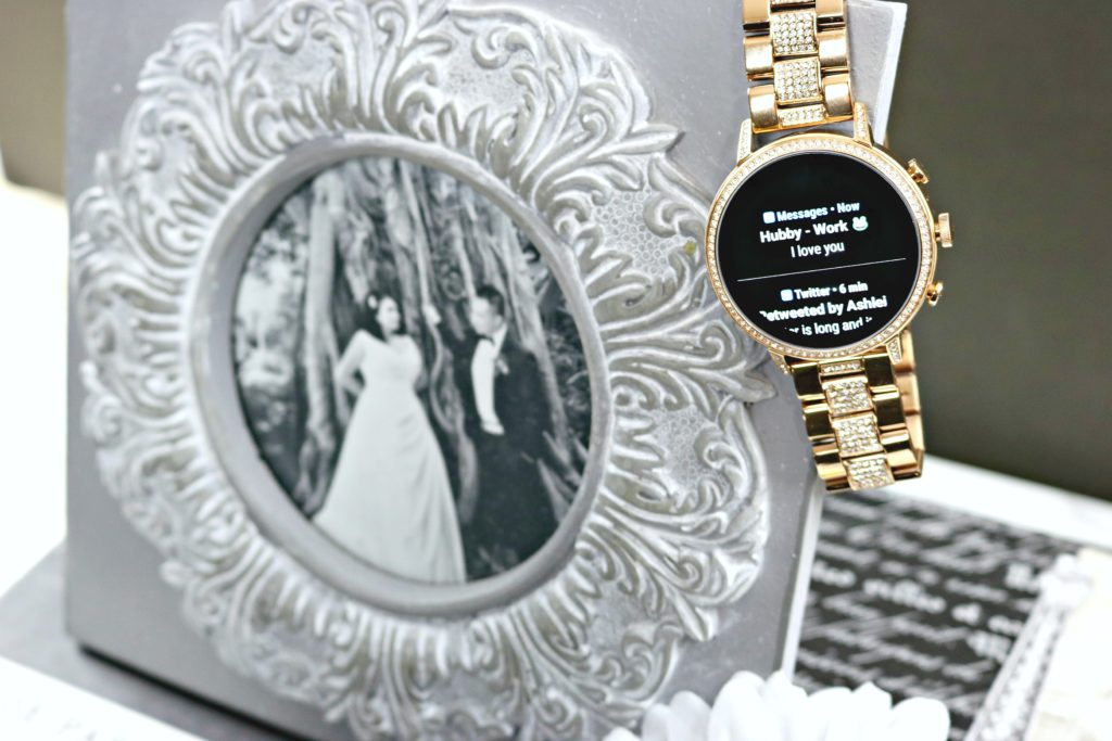 A text is seen on the Fossil smartwatch that is hanging from a picture frame.