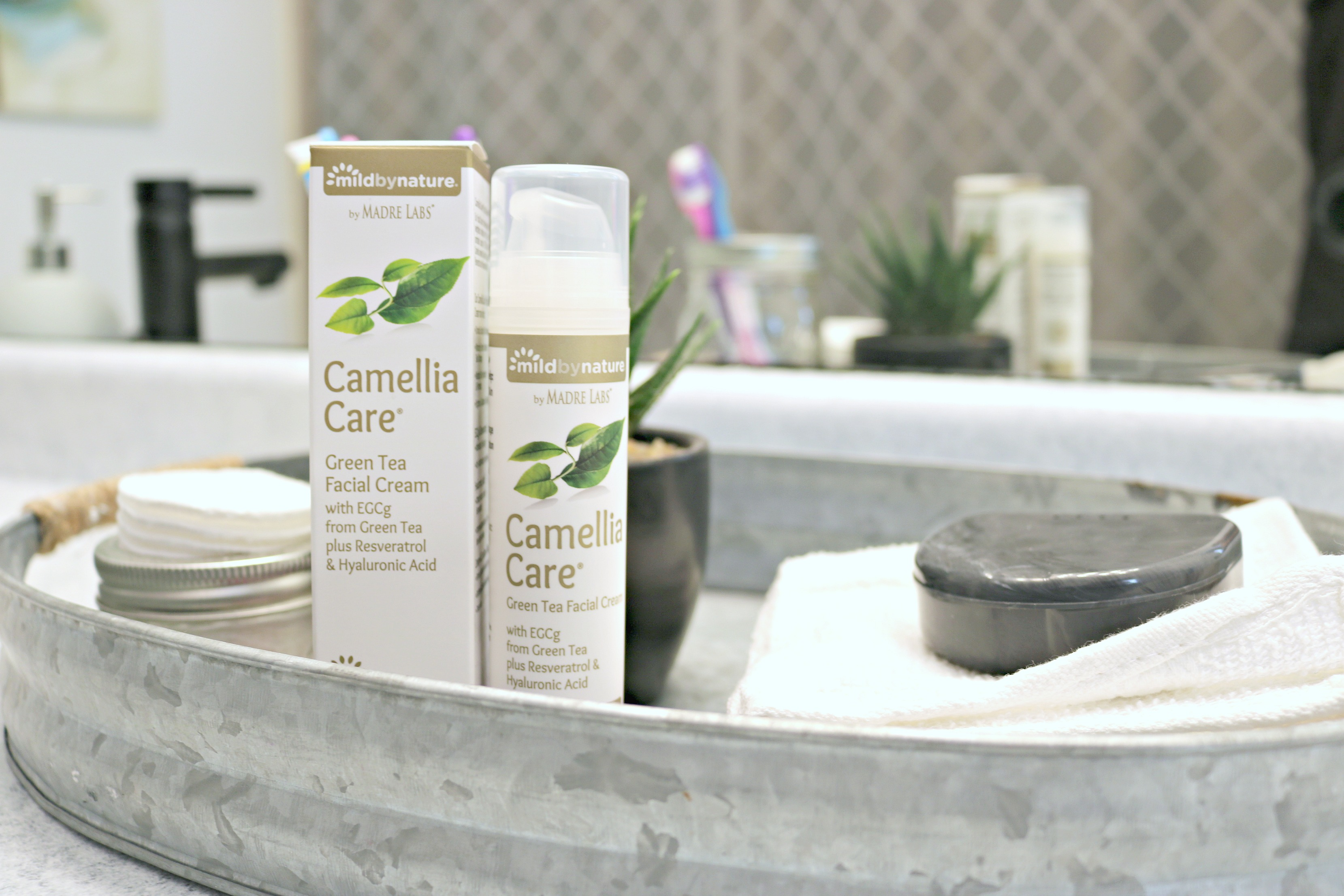Camellia Care Green Tea Facial Cream in a washroom along with other necessities.