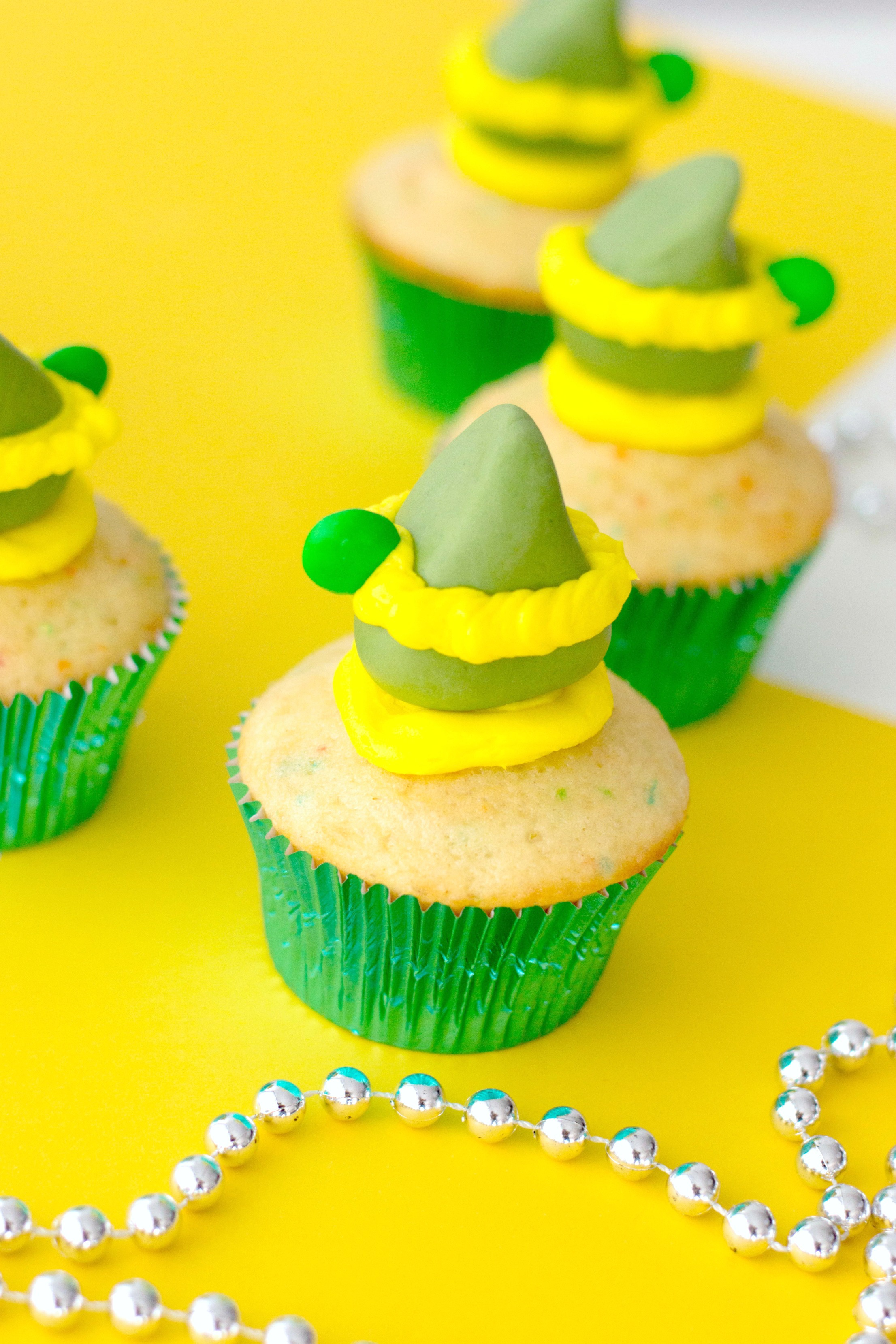 Buddy the Elf inspired funfetti cupcakes on a yellow table with silver garland.