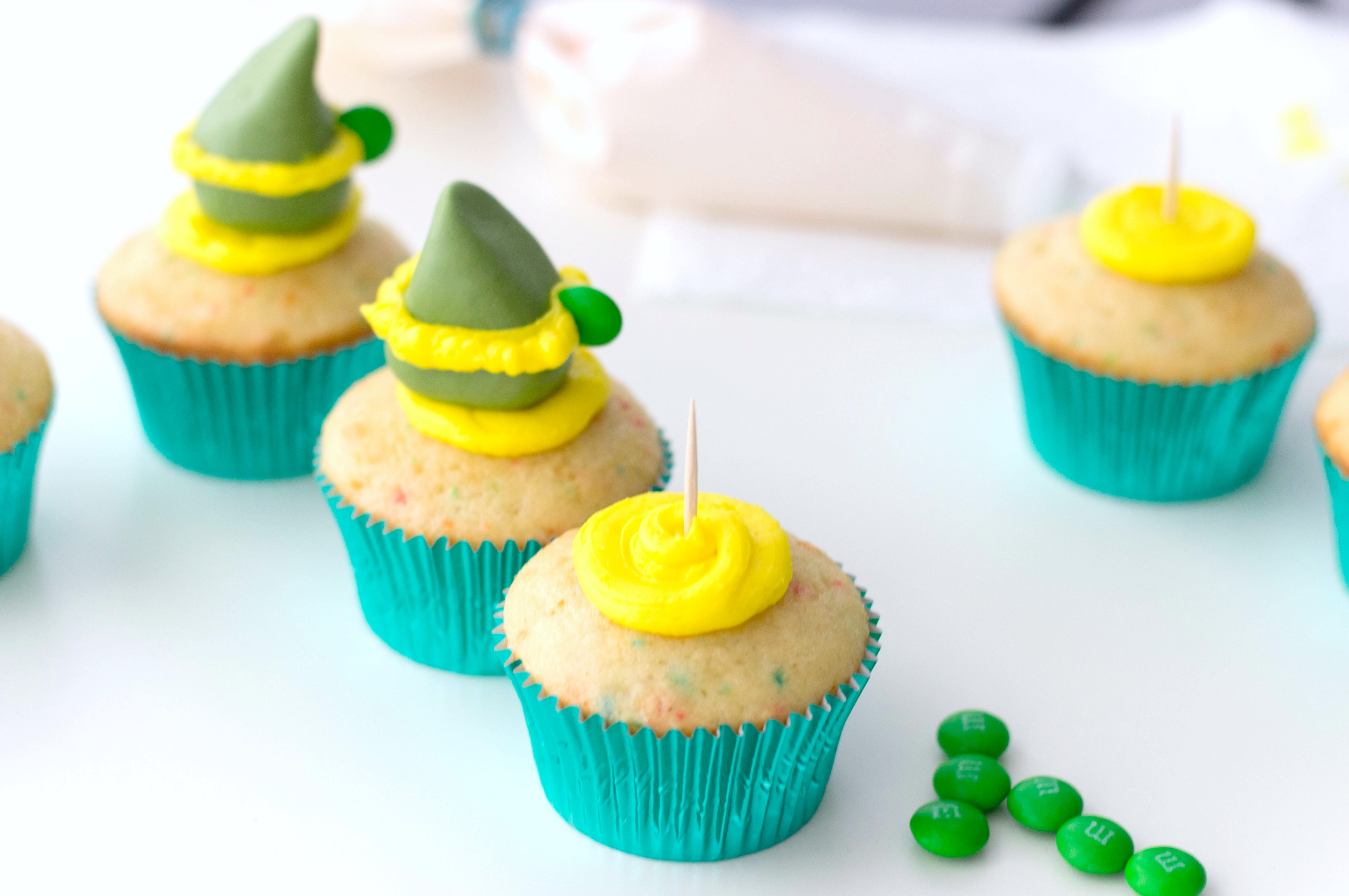 Funfetti cupcakes with a toothpick placed in the middle of buttercream to hold fondant elf hat.
