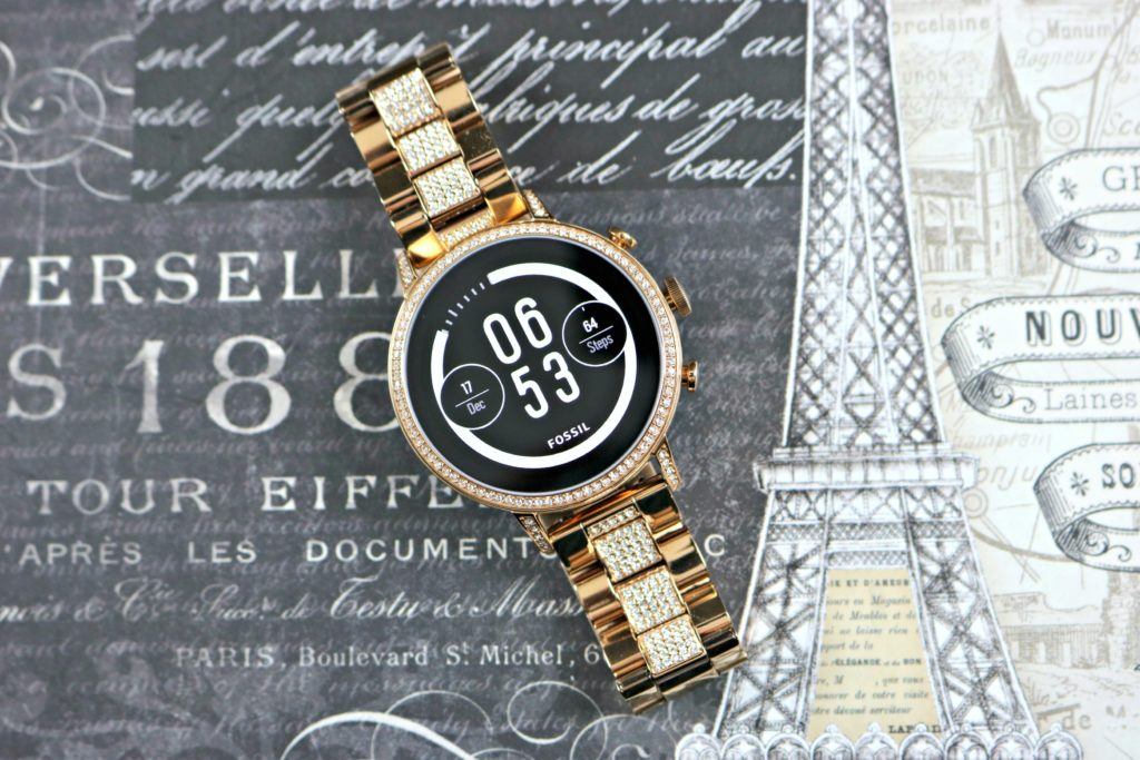 A smartwatch with a sleek face is shown on a Paris background.