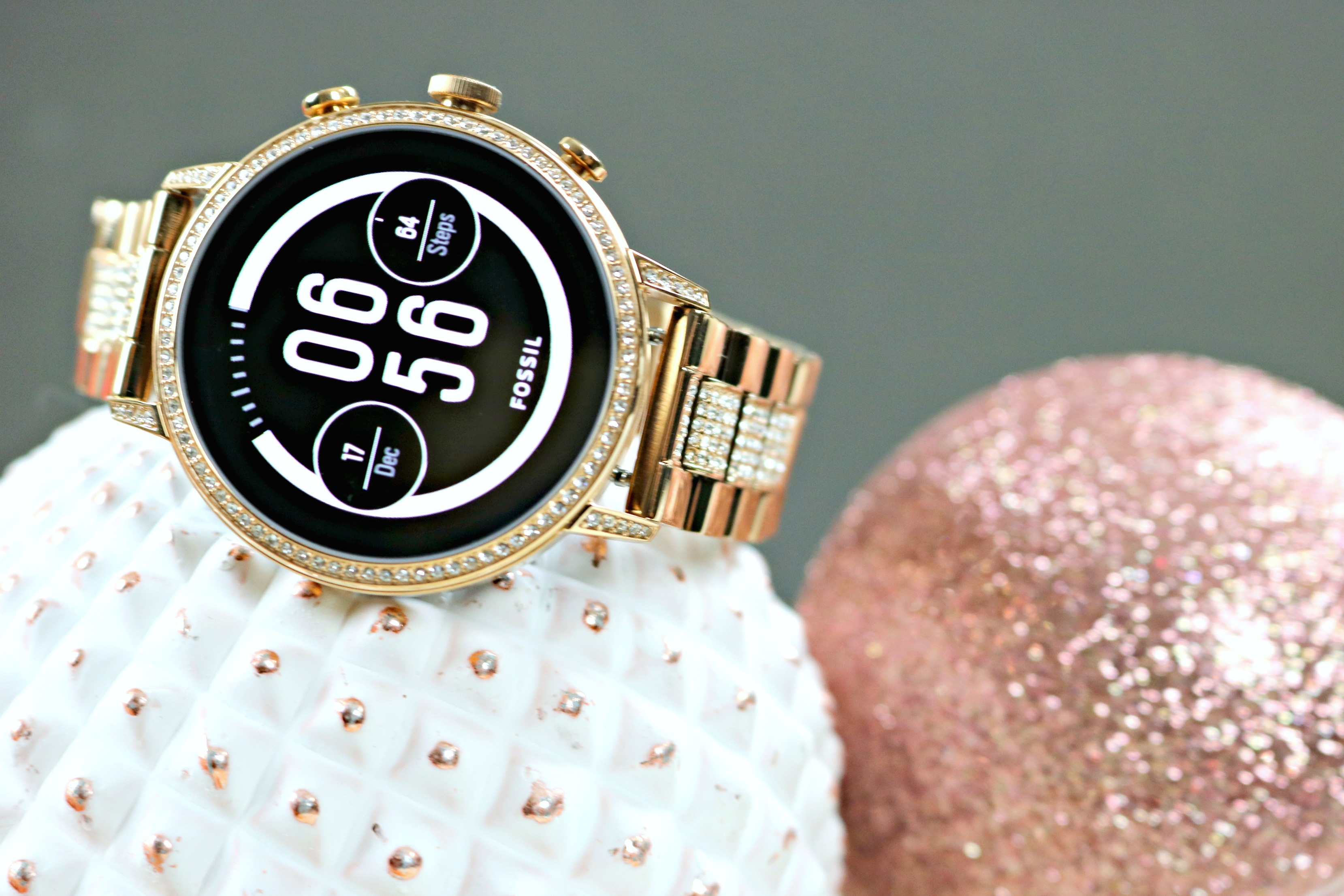 Fossil Smartwatch sitting on top of rose gold ornaments.