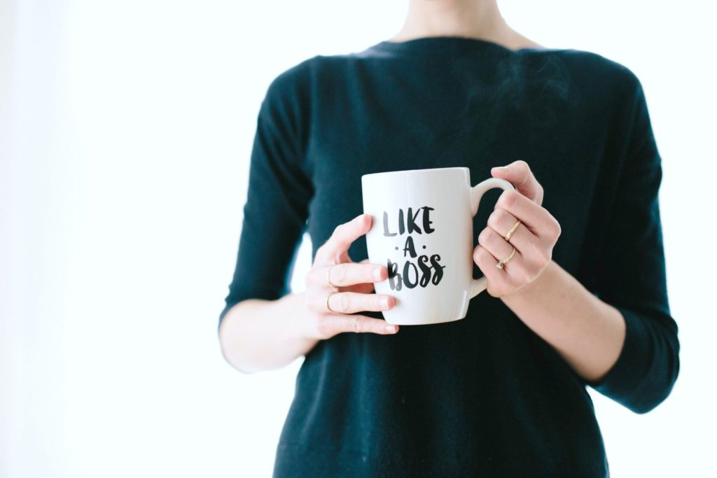 A woman holds a mug that says 'Like a Boss'.
