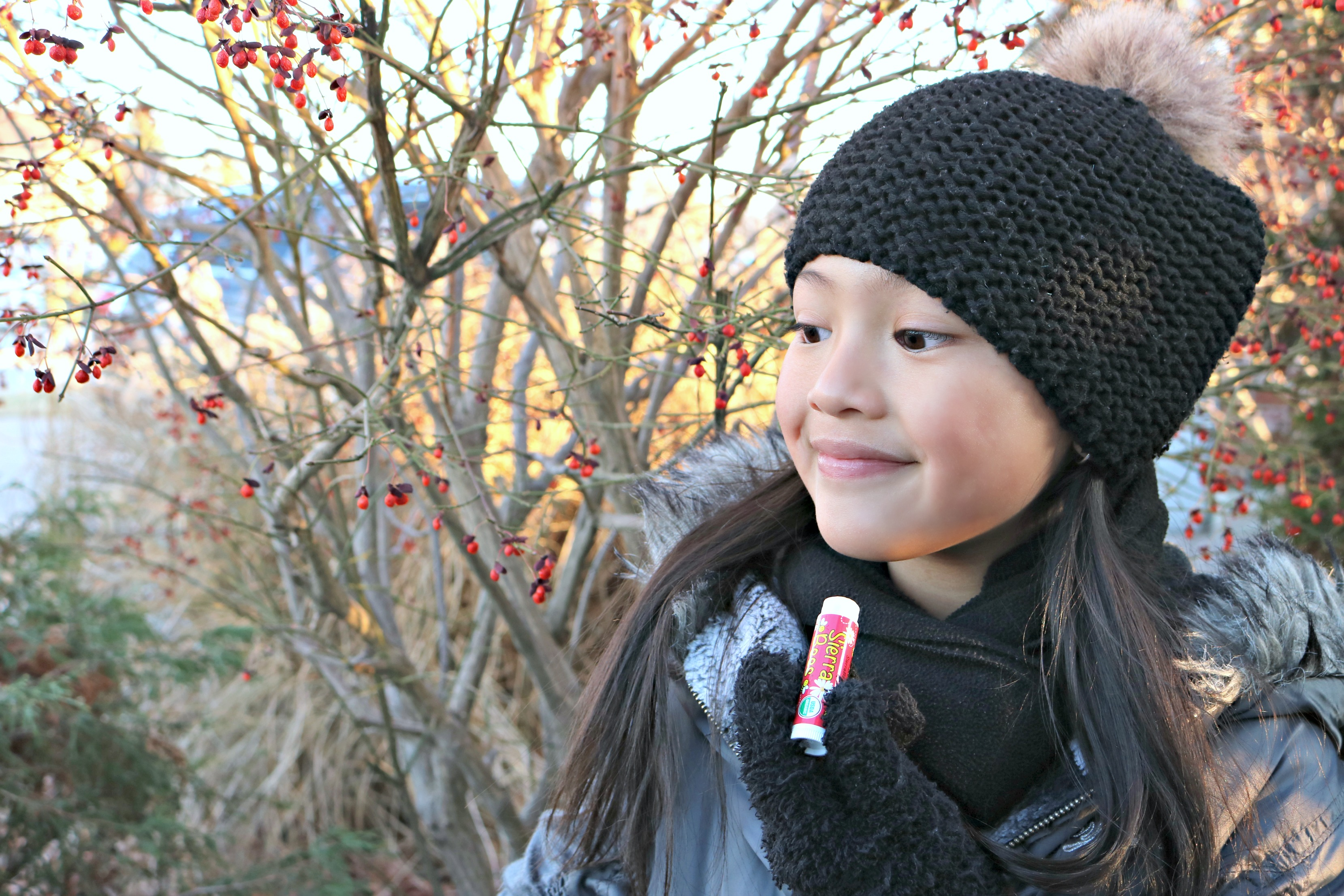 Little girl holds Sierra Bees Organics chap stick.