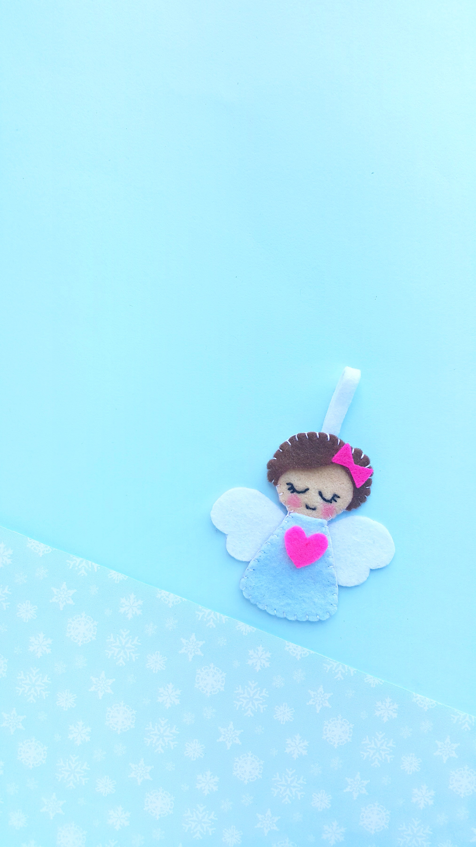 A felt angel Christmas ornament is laying on a blue background with white snowflakes.