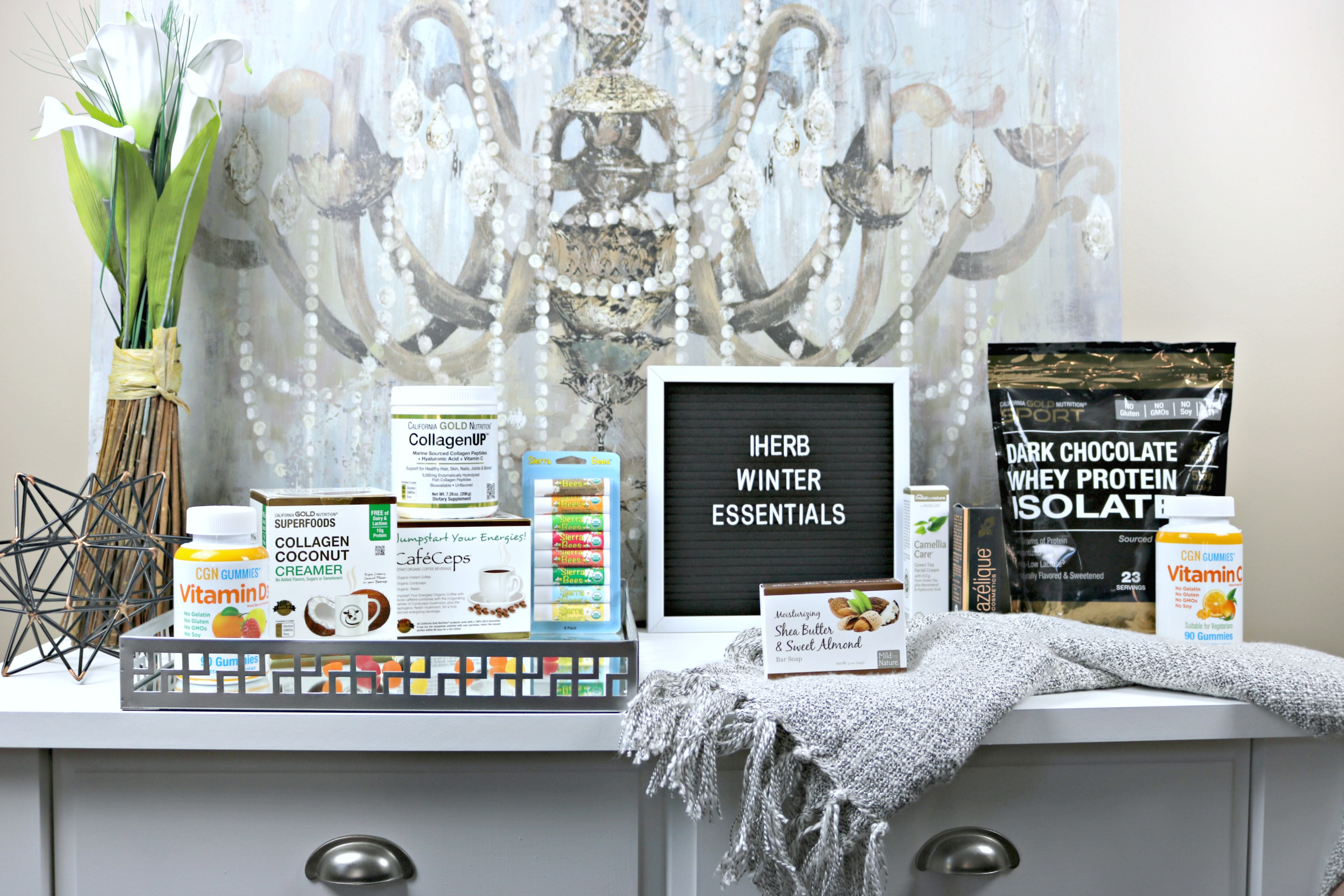 iHerb Winter Essentials on a buffet table and tray: Vitamins, coffee, creamer, vitamins, beauty products and more.