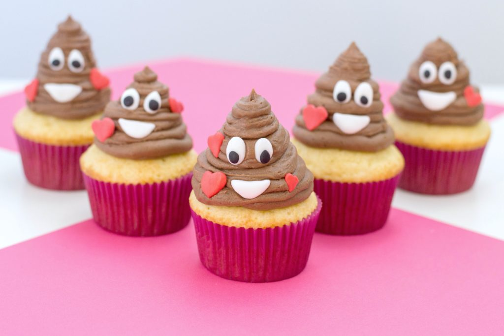5 poop emoji cupcakes are shown on a pink and white table.