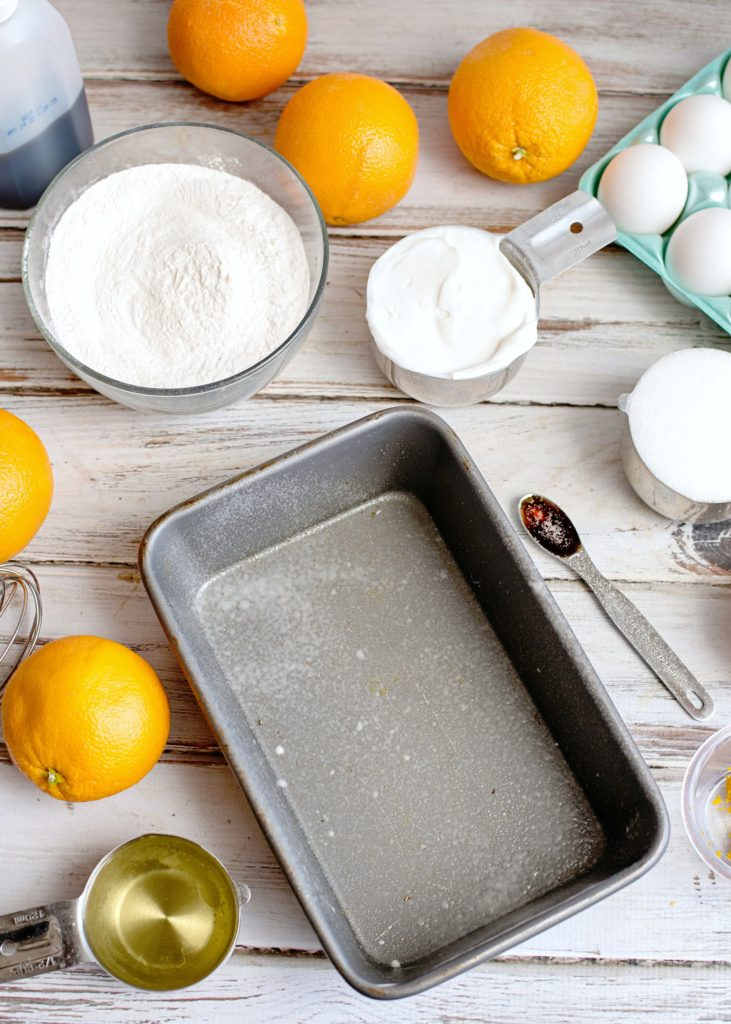 Ingredients to make glazed orange bread, with a greased loaf pan.