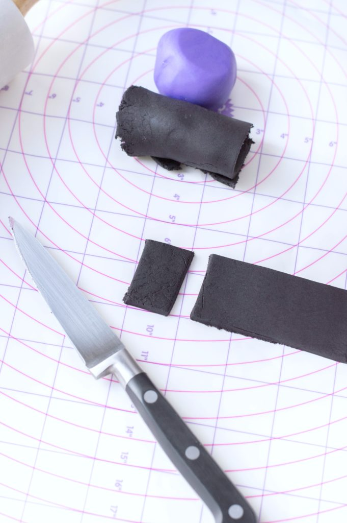 A ball of purple fondant and black fondant are shown, a knife is pictured cutting rectangles out of flattened and measured black fondant.