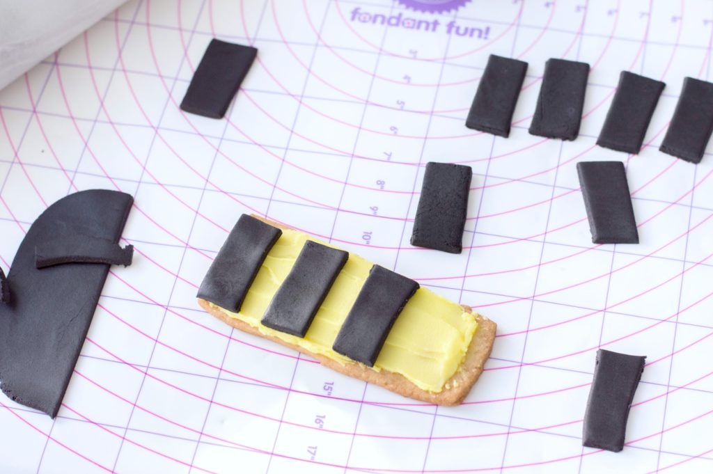 Black fondant rectangles are being placed on iced sugar cookie.