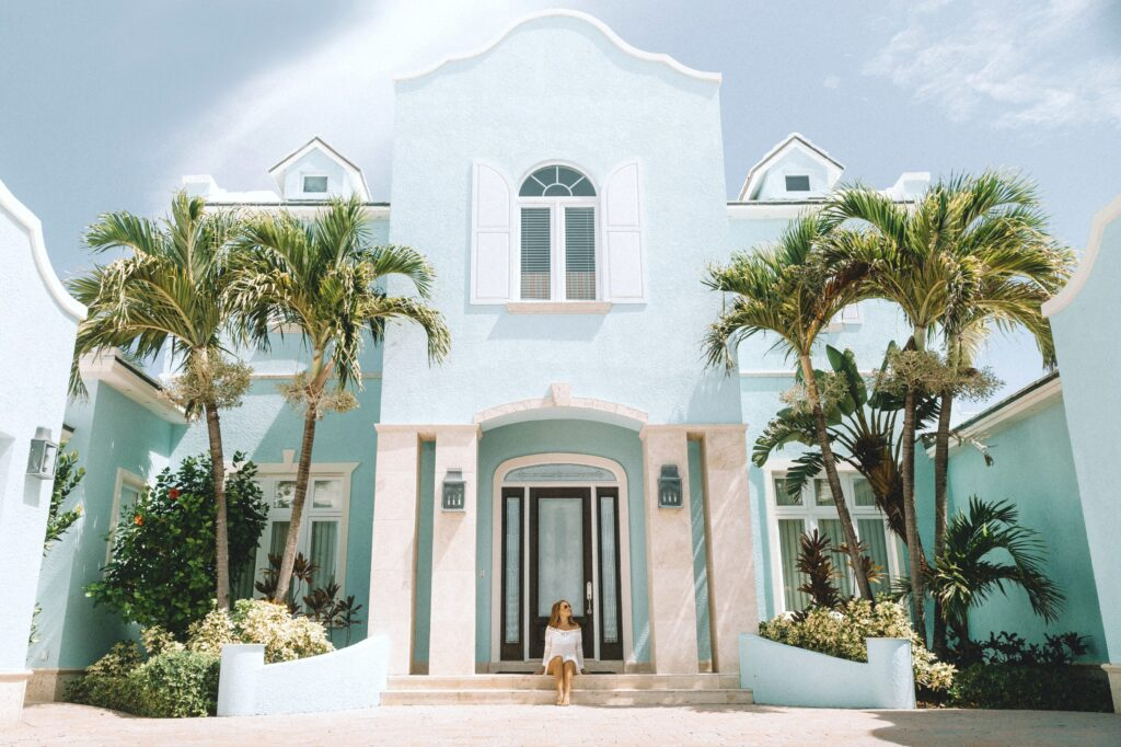 Woman sits in the front step of her large pastel blue and white house.