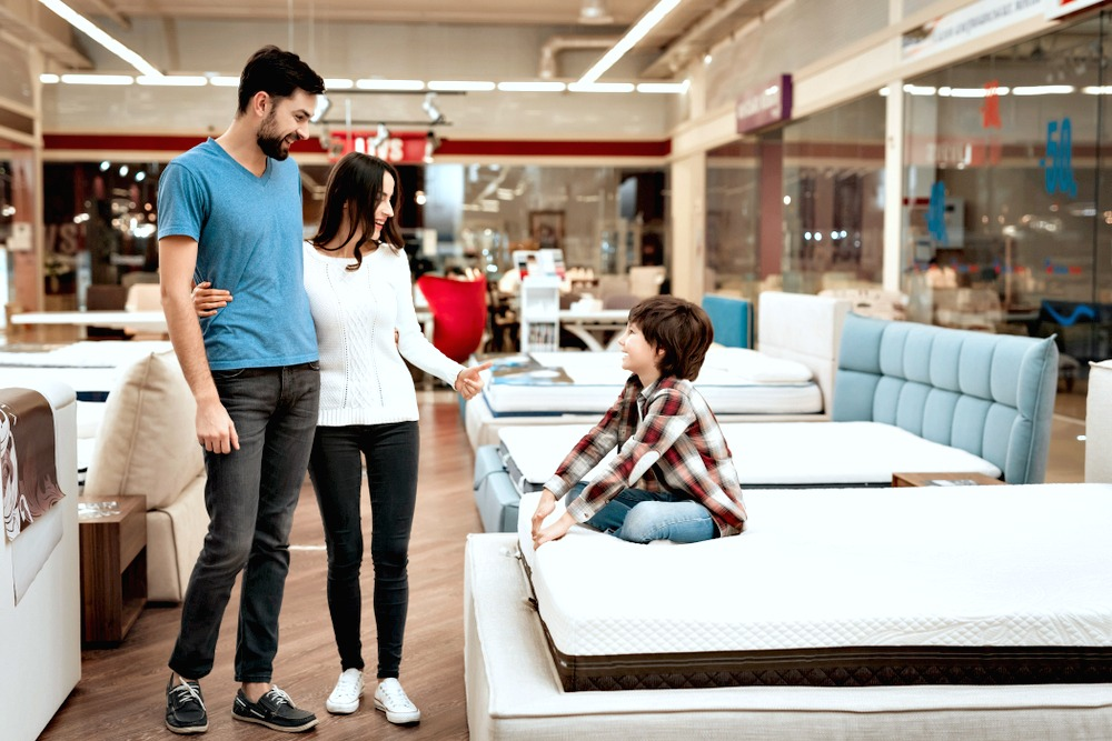 A couple with a young boy browse for new furniture.
