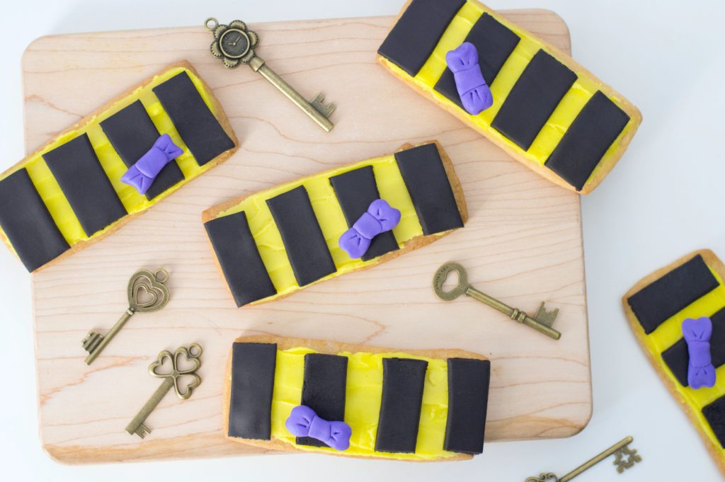 Hufflepuff sugar cookies adorned with Newt Scamander's bowtie. Placed on a wood tray with whimsical skeleton keys.