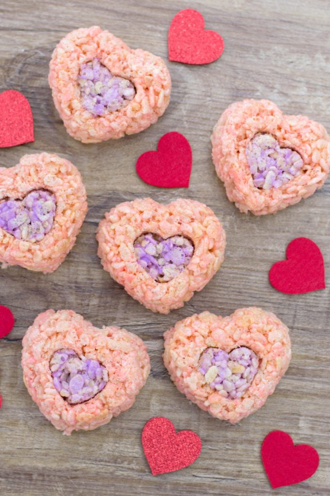 Valentine's rice cereal treats in shape of hearts on wood background with red hearts surrounding them.