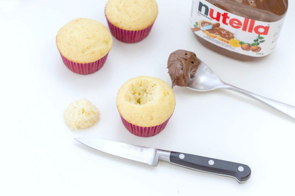 The top center of the cupcake is cut out with a knife and a spoon of nutella is shown.