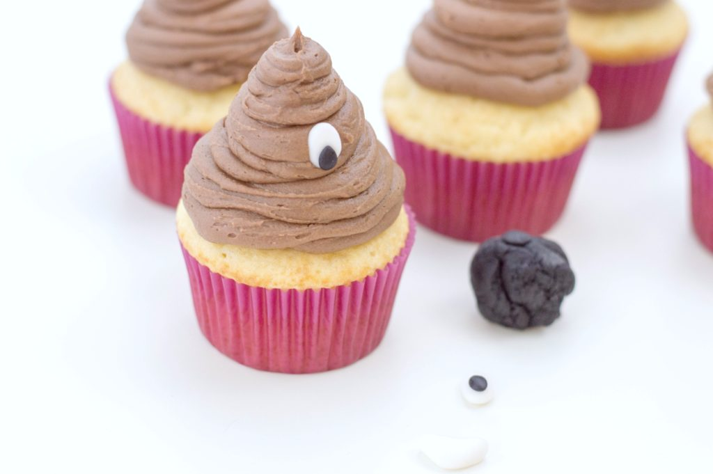 Cupcakes are shown with frosting added in shape of poop emoji and fondant eyes being added.
