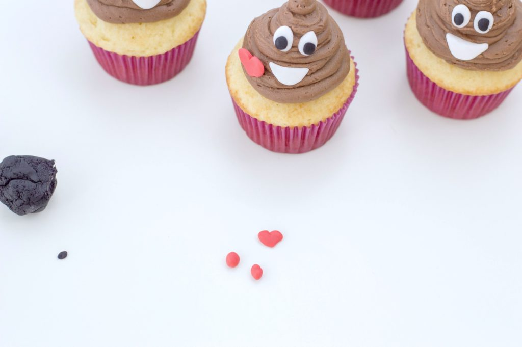 Adding little hearts to the poop emoji cupcake.