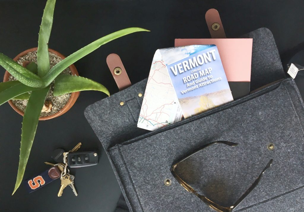 Messenger bag with Vermont road map, flat lay with keys, plant, and sunglasses.