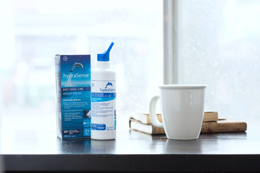 A hydraSense bottle next to a white mug and a stack of books.