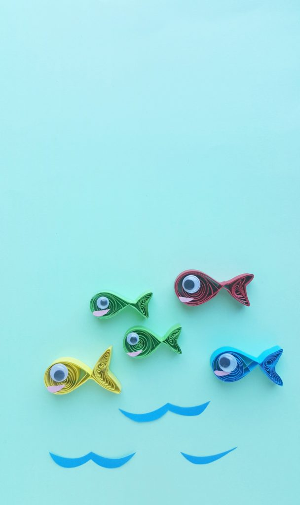 One fish, two fish, red fish, blue fish in quilled paper form. Blue construction paper waves against a blue background.