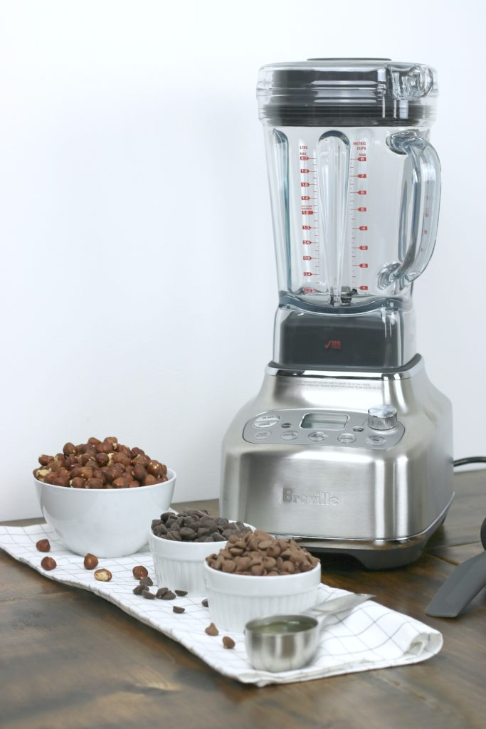 The Breville Super Q blender with 4 ingredients for hazelnut spread recipe. Hazelnuts, dark chocolate, milk chocolate, and peanut oil.