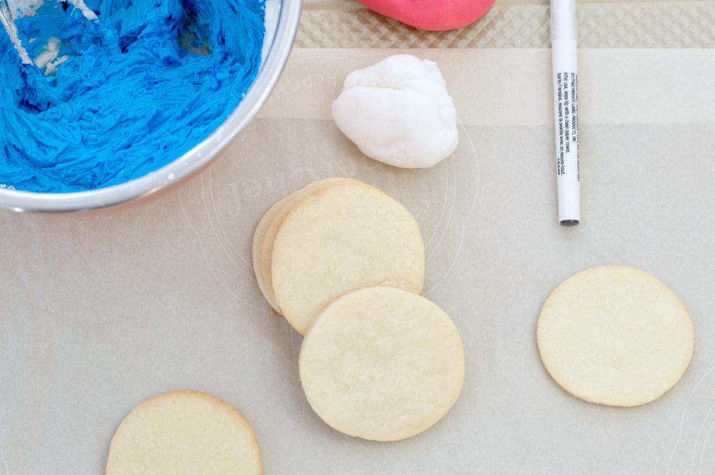 Plain sugar cookies ready to be iced, a bowl of bright blue icing and red and white fondant are pictured.