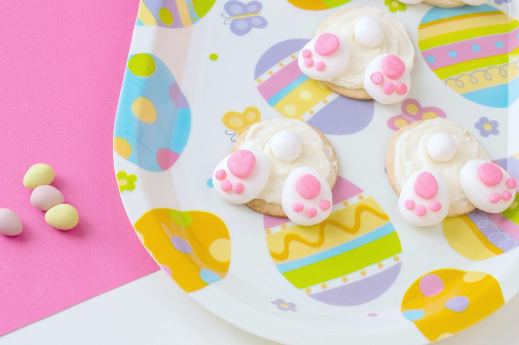 3 completed bunny bum cookies are shown a very festive Easter plate on a pink and white backdrop. Chocolate mini eggs are pictured.